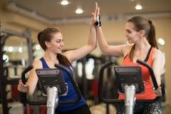 Twee vrolijke meisjes die samen in de club van de gymnastieksport uitoefenen stock foto