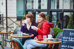 Twee vrolijke meisjes in een Parijse straatkoffie Royalty-vrije Stock Afbeeldingen