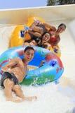 Twee vrolijke meisjes en jongensaandrijving met buis op de rafting dia Stock Foto