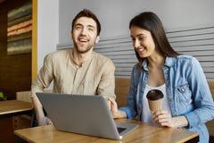 Twee vrolijke studenten met donkere haarzitting in cafetaria, het drinken koffie en lachen, die video van yesterday ` s kijken Stock Afbeelding