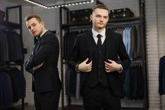 Twee vrolijke vrienden in klassiek vest tegen rij van kostuums in winkel Stock Fotografie