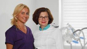 Twee vrolijke vrouwelijke artsen die aan de camera bij het ziekenhuis glimlachen royalty-vrije stock afbeelding