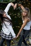 Twee vrolijke vrouwen die hartvorm met handen maken Royalty-vrije Stock Foto's