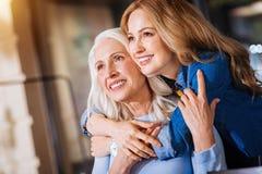 Twee vrolijke vrouwen die van verschillende leeftijd de afstand onderzoeken royalty-vrije stock foto's