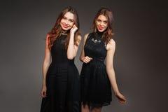 Twee vrolijke vrouwen in zwarte kleding die naar partij samen gaan Stock Foto