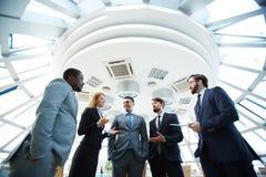 Twee vrolijke zakenlieden die over zaken spreken terwijl één van hen die computermonitor richten Stock Foto