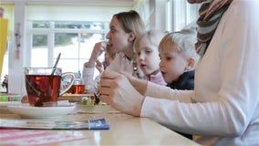 Twee vrouw en twee kinderen eten bij de lijst stock video