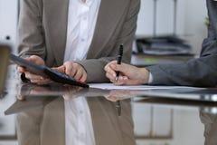 Twee vrouwelijke accountants die op calculatorinkomen tellen voor belasting vormen voltooiing, handenclose-up De de fiscusdienst stock foto