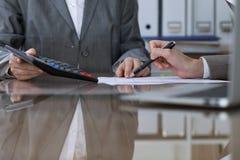 Twee vrouwelijke accountants die op calculatorinkomen tellen voor belasting vormen voltooiing, handenclose-up De de fiscusdienst royalty-vrije stock afbeeldingen