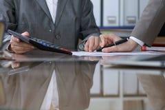 Twee vrouwelijke accountants die op calculatorinkomen tellen voor belasting vormen voltooiing, handenclose-up De de fiscusdienst stock foto's