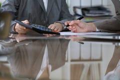Twee vrouwelijke accountants die op calculatorinkomen tellen voor belasting vormen voltooiing, handenclose-up De de fiscusdienst stock afbeeldingen