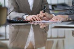 Twee vrouwelijke accountants die op calculatorinkomen tellen voor belasting vormen voltooiing, handenclose-up De de fiscusdienst royalty-vrije stock foto