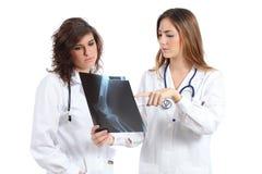 Twee vrouwelijke artsen die op een radiografie letten royalty-vrije stock afbeeldingen