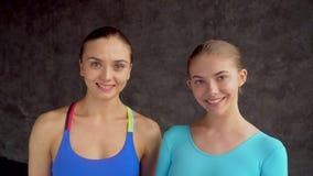 Twee vrouwelijke atleten die de camera, portret bekijken close-upsport, fitness, emotie, uitdrukking en mensenconcept - stock footage