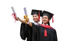 Twee vrouwelijke Aziatische studenten in graduatietoga stock foto's