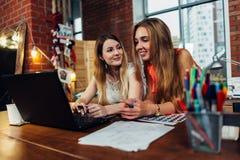 Twee vrouwelijke bloggers die een vriendschappelijk gesprek hebben die nieuwe ideeën bespreken die voor computer zitten thuis met royalty-vrije stock foto's