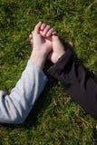 Twee vrouwelijke handen, moeder en saughter houdt elkaar het liggen in gras overhandigt Royalty-vrije Stock Fotografie