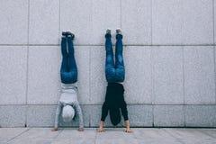 Twee vrouwelijke hipsters die handstand doen Stock Afbeeldingen