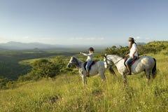 Twee vrouwelijke horseback ruiters op horseback berijden bij zonsondergang aangezien men het overzien van de vallei van Lewa-het  Stock Afbeelding