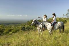 Twee vrouwelijke horseback ruiters op horseback berijden bij zonsondergang die Lewa-het Wildmilieubescherming in Noord-Kenia, Afr Stock Afbeelding
