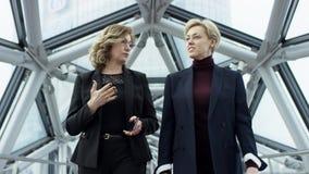 Twee vrouwelijke onderneemsters in formele clothesare die en Zaken lopen bespreken Zij allen werken in Centrale Zaken stock footage
