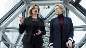 Twee vrouwelijke onderneemsters lopen en bespreken zaken Zij allen werken in centraal bedrijfsdistrict Zij zijn stock footage