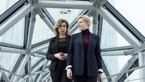 Twee vrouwelijke onderneemsters lopen en bespreken zaken Zij allen werken in centraal bedrijfsdistrict Zij zijn stock videobeelden