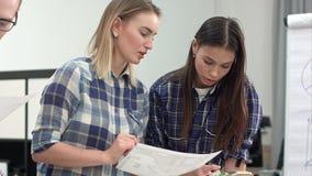 Twee vrouwelijke ontwerpers die lay-out en kleurensteekproeven bespreken stock video