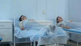 Twee vrouwelijke patiënten op druppels die op bedden in het ziekenhuisafdeling die liggen door twee artsen worden gecontroleerd stock videobeelden