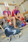 Twee vrouwelijke spelers van het rolhockey in kleedkamer stock afbeeldingen