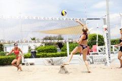 Twee vrouwelijke spelers van het strandvolleyball Aanval en defensie stock afbeelding