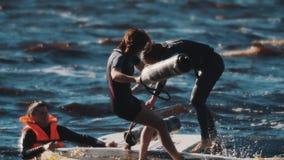 Twee vrouwelijke surfers die met zachte knuppels op surfende raad in golvend water vechten stock footage