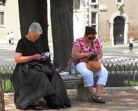 Twee vrouwelijke toeristen die een onderbreking op een bank in Rome nemen stock foto