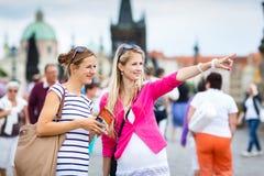 Twee vrouwelijke toeristen die langs Charles Bridge lopen Royalty-vrije Stock Foto