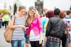 Twee vrouwelijke toeristen die langs Charles Bridge lopen royalty-vrije stock afbeelding