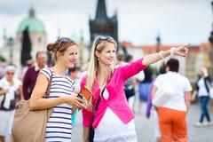 Twee vrouwelijke toeristen die langs Charles Bridge lopen royalty-vrije stock foto's