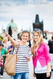 Twee vrouwelijke toeristen die langs Charles Bridge lopen stock foto