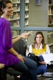 Twee vrouwelijke universitaire studenten die in bibliotheek spreken royalty-vrije stock foto's