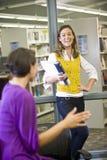 Twee vrouwelijke universitaire studenten die in bibliotheek spreken Royalty-vrije Stock Foto