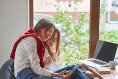 Twee vrouwelijke vrienden bij de koffie stock afbeelding