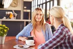 Twee vrouwelijke vrienden die bij een koffiewinkel spreken Royalty-vrije Stock Afbeeldingen