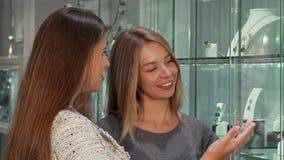 Twee vrouwelijke vrienden die juwelen kiezen om bij de opslag te kopen stock video