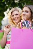 Twee vrouwelijke vrienden die met het winkelen zakken glimlachen stock afbeeldingen