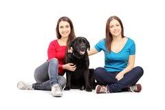 Twee vrouwelijke vrienden die op een vloer zitten en met een hond stellen stock afbeelding