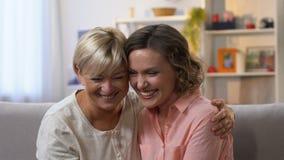 Twee vrouwelijke vrienden die op laag lachen, en pret hebben, langzaam-mo samen roddelen stock videobeelden