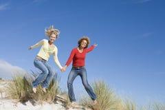 Twee vrouwelijke vrienden die pret op strand hebben Stock Afbeelding