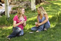Twee vrouwelijke vrienden die samen speelkaarten zitten stock afbeeldingen