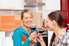 Twee vrouwelijke vrienden die zich in een flat bewegen Stock Afbeelding