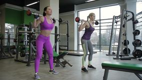 Twee vrouwelijke vrienden doen terug hurkzit in moderne gymnastiek stock videobeelden