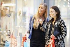 Twee Vrouwelijke Vrienden met Zakken in Winkelcomplex stock afbeeldingen